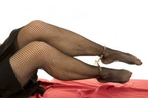 Woman legs blck fishnet cuffs on ankles
